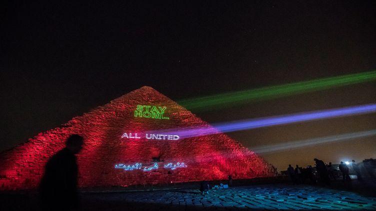 La pyramide s'est illuminée pour inciter les gens à rester chez eux et honorer ceux qui les protègent. (KHALED DESOUKI / AFP)