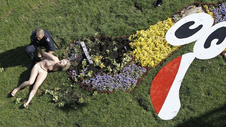 Une féministe du mouvement Femen est arrêtée par un policier devant la mascotte fleurie de l'Euro, à Kiev (Ukraine), le 31 mai 2012. (GLEB GARANICH / REUTERS)
