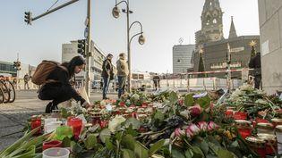 Des passants déposent des fleurs et des bougies près du lieu de l'attaque au camion-bélier à Berlin (Allemagne), le 21 décembre 2016. (CLEMENS BILAN / AFP)