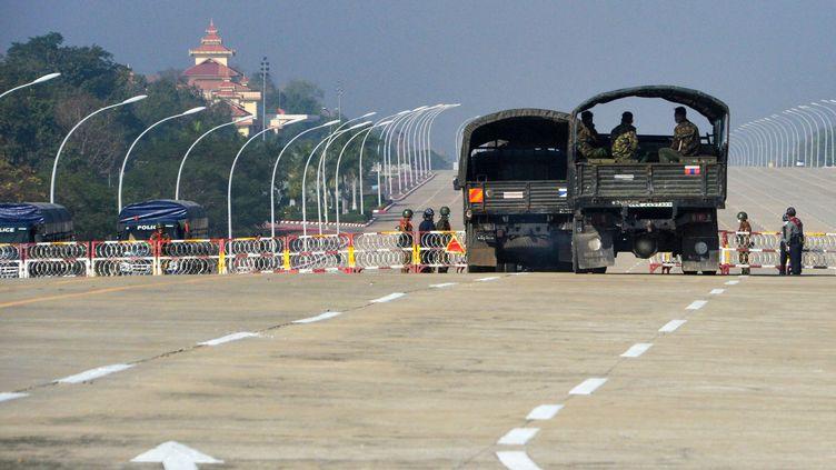 Des soldats bloquant une route allant au parlement birman, à Naypyidaw, après le coup d'Etat du 1er février 2021 (STR / AFP)