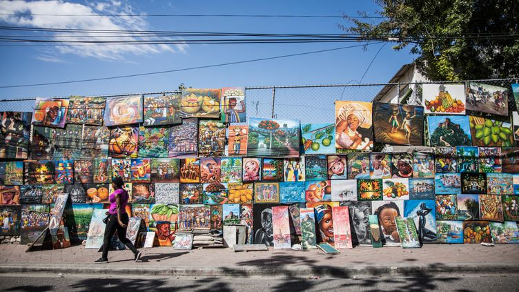 Une femme passe devant une fresque murale à Port-au-Prince (Haïti), le 15 février 2021. (VALERIE BAERISWYL / AFP)