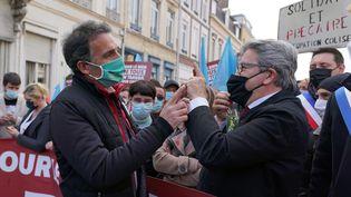 """Le déouté """"insoumis"""" des Bouches-du-Rhône Jean-Luc Mélenchon (à droite) discute avec le maire écologiste de Grenoble, Eric Piolle (à gauche), le 1er mai 2021, dans le cortège à Lille. (SYLVAIN LEFEVRE / HANS LUCAS / AFP)"""