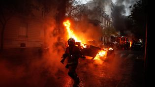 """Un pompier devant une voiture incendiée lors de la manifestation des """"gilets jaunes"""" à Paris, le 1er décembre 2018. (ABDULMONAM EASSA / AFP)"""