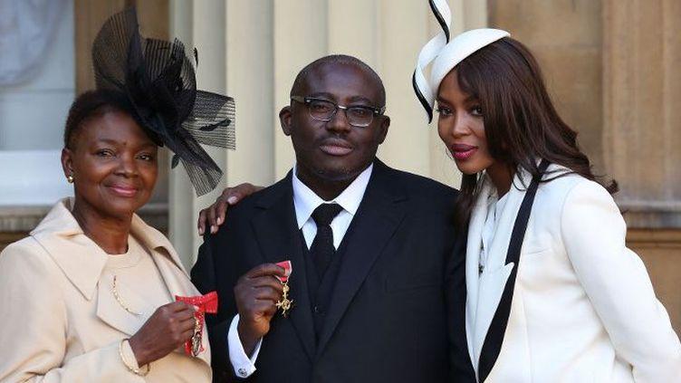 Edward Enninful, fait officier de l'ordre de l'Empire britannique en octobre 2016 pour sa contribution à la diversité dans la mode, pose entre la baronne Amos (g), elle aussi décorée, et sa grande amie, le mannequin Naomi Campbell. (Philip Toscano / POOL / AFP)