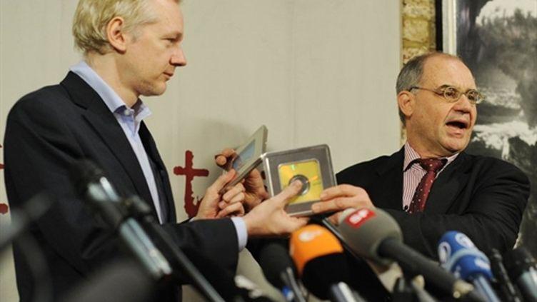 L'ex-banquier suisse Rudolf Elmer (à droite) remet à Julian Assange les noms de potentiels fraudeurs du fisc (AFP/Ben STANSALL)