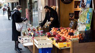 Une femme achète des fruits et légumes, le 25 mars 2020, à Paris. (EMERIC FOHLEN / NURPHOTO / AFP)