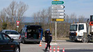 Des gendarmes près des lieux de la prise d'otages, le 23 mars 2018 à Trèbes (Aude). (ERIC CABANIS / AFP)