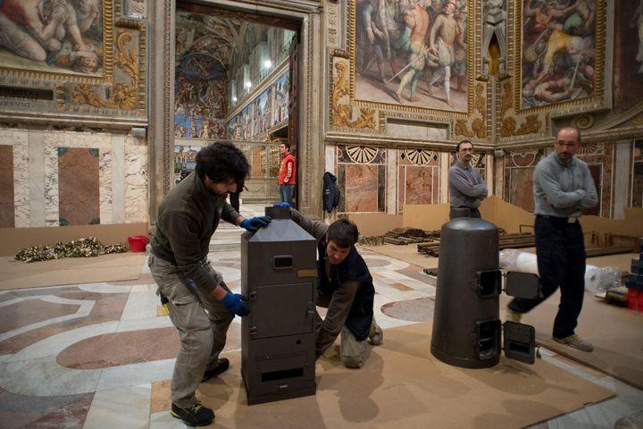 Des ouvriers installent les deux poêles dans la chapelle Sixtine, au Vatican, le 7 mars 2013. (OSSERVATORE ROMANO / REUTERS)