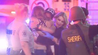 un groupe de jeunes se prennent dans les bras après la fusillade qui a fait 12 morts dans une discothèque près de Los Angeles, en Californie (États-Unis), dans la soirée du mercredi 7 novembre. (FRANCE 3)