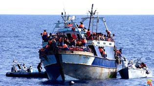 Un navire chargé de migrants arraisonné par la marine italienne, le 4 août 2014, en Mediterranée. (MARINA MILITARE / AFP)