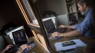 Un homme en télétravail participe à une viséoconference depuis son domicile. Photo d'illustration. (LOIC VENANCE / AFP)