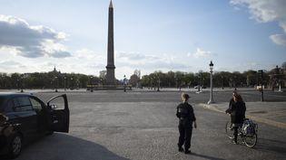 Des policiers vérifient l'attestation de déplacement dérogatoire d'une cycliste sur la place de la Concorde, à Paris, le 18 mars 2020. (NICOLAS PORTNOI / HANS LUCAS / AFP)