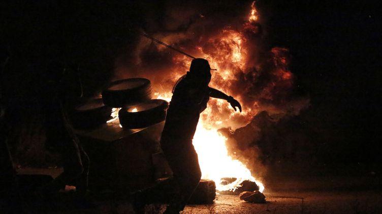 Un Palestinien lance des pierres sur des soldats israéliens lors d'affrontements à Ramallah, en Cisjordanie occupée, le 4 octobre 2015. (ABBAS MOMANI / AFP)
