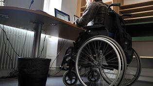 Un homme handicapé à son bureau. (MYCHELE DANIAU / AFP)