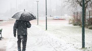 Un passant marche sous la neige à Annecy (Haute-Savoie), le 27 décembre 2014. (ANTHONY DEPERRAZ / CITIZENSIDE / AFP)