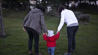 Un couple de femmes prenant un enfant par la main au Portugal dans un parc, en 2014. (PATRICIA DE MELO MOREIRA / AFP)