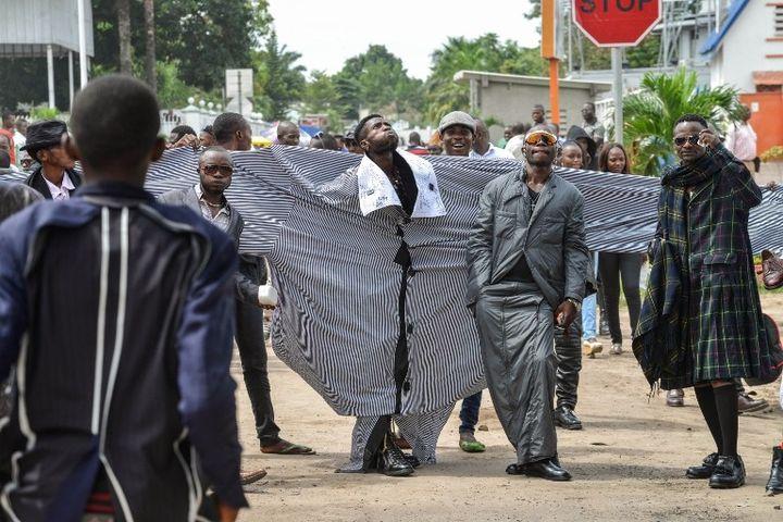Un membre de La Sape porte une chemise avec des manches longues de 4 mètres.  (JUNIOR D. KANNAH / AFP)