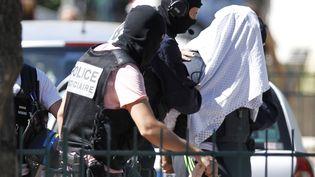 Yassin Salhi, la tête recouverte d'un drap, est escorté par deux policiers àSaint-Priest (Rhône), le 28 juin 2015. (EMMANUEL FOUDROT / REUTERS)