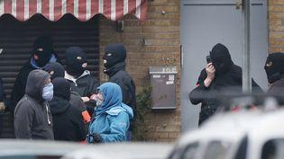 Des policiers bloquent une rue de Molenbeek, le 18 mars 2016, près de Bruxelles (Belgique), le jour de l'arrestation de Salah Abdeslam. (FRANCOIS LENOIR / REUTERS)