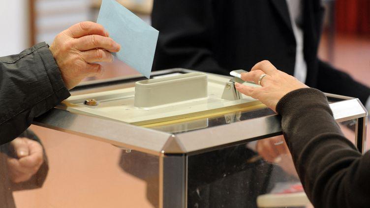 Illustration d'un bulletin de vote glissé dans l'urne lors des élections régionales de décembre 2015 en Bretagne. (FRED TANNEAU / AFP)