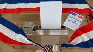 Une écharpe tricolore, une urne, une carte électorale et une enveloppe.Symboles d'une élection municipale. Photo d'illustration. (THIERRY THOREL / MAXPPP)