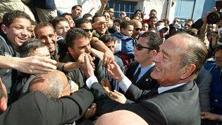 Le président français Jacques Chirac serre la main de ses partisans le 3 mars 2003 à Alger. (PATRICK KOVARIK / AFP)
