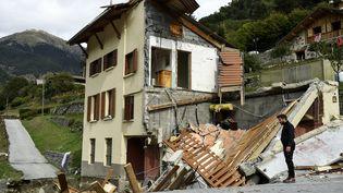 Un homme se tient à côté d'une maison détruite à Saint-Martin-Vésubie par les inondations causées par la tempête Alex, le 6 octobre 2020. (NICOLAS TUCAT / AFP)