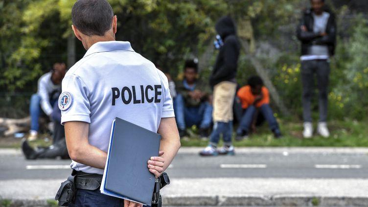 Un policier surveillant des migrants au bord de la route, près du port de Calais (Pas-de-Calais), le 16 août 2017. (PHILIPPE HUGUEN / AFP)