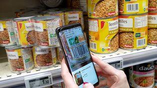 Un consommateur utilise l'application Yuka dans un supermarché de Valence (Drôme), le 11 novembre 2019. (NICOLAS GUYONNET / HANS LUCAS / AFP)