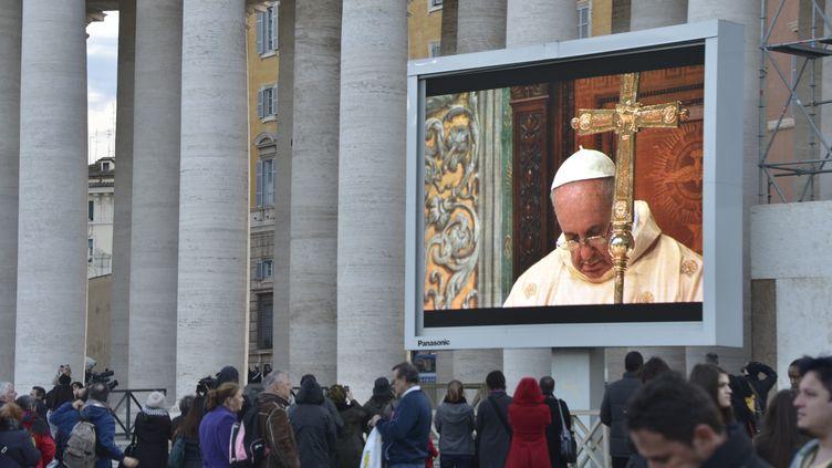 Les fidèles regardent sur un grand écran la première messe du pape François,dans la chapelle Sixtine, le 14 mars 2013. (JOHANNES EISELE / AFP)