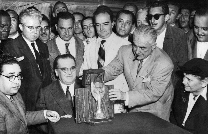 Les représentants de la fédération italienne, dont Ottorino Barassi (assis, cravate sombre), transmettent le trophée à leurs homologues brésiliens, organisateurs de la compétition qui va démarrer, le 22 juin 1950, à Rio de Janeiro (Brésil). (STAFF / INTERCONTINENTALE / AFP)