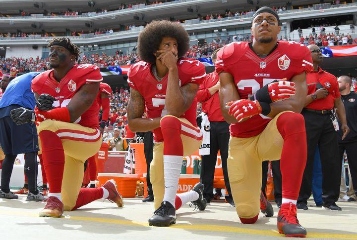 Les joueurs de football américain Eli Harold, Colin Kaepernick et Eric Reid (de gauche à droite), agenouillés durant l'hymne américain, le 2 octobre 2016, à Santa Clara (Californie). (THEARON W. HENDERSON / GETTY IMAGES NORTH AMERICA)