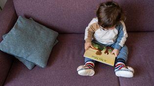 Un garçon de 19 mois joue tout seul sur un canapé (illustration). (RICCARDO MILANI / HANS LUCAS / AFP)
