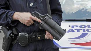 Un policier tient un Flash-Ball, durant un exercice à La Courneuve (Seine-Saint-Denis), le 2 juillet 2009. (BERTRAND GUAY / AFP)