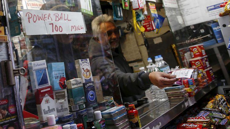 Un homme vend un ticket pour la loterie du Powerball, le 7 janvier 2016, à New York (Etats-Unis). (SHANNON STAPLETON / REUTERS)