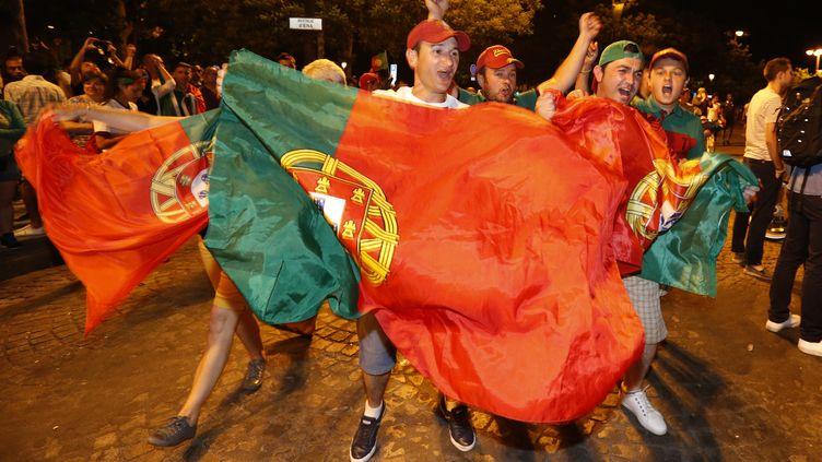 Des supporters portugais fêtent la victoire de leur équipe à l'Euro, dimanche 10 juin 2016, sur l'avenue des Champs-Elysées à Paris. (REGIS DUVIGNAU / REUTERS)