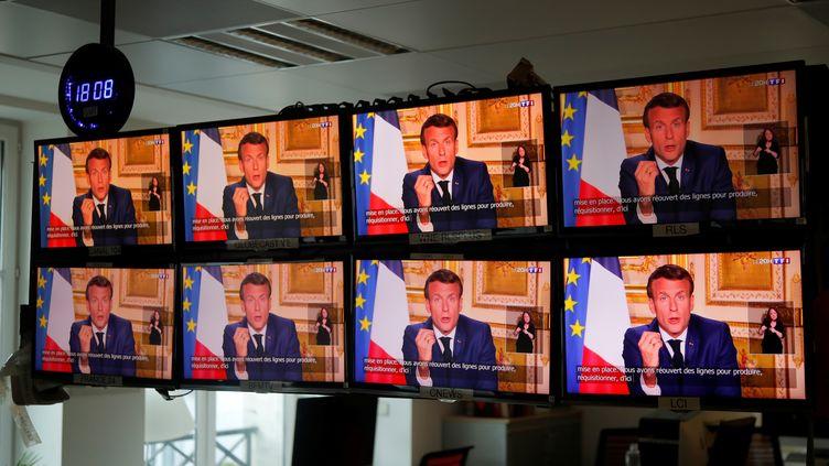 Emmanuel Macron diffusé sur des écrans à Paris lors d'une prise de parolesur la crise sanitaire, le 13 avril 2020. (CHARLES PLATIAU / REUTERS)