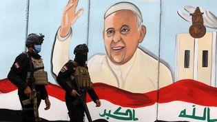 Des membres des forces spéciales irakiennes surveillent une église catholique syriaque de Bagdad (Irak), jeudi 4 mars, à la veille de l'arrivée dans la ville du pape François. (AHMAD AL-RUBAYE / AFP)