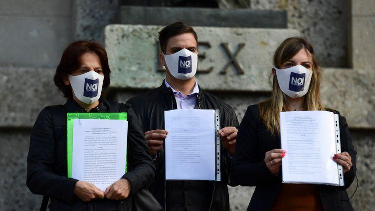 """Des membres du comité """"Noi Denunceremo"""" (Nous dénoncerons), devant le palais de justice de Bergame, en Italie. (MIGUEL MEDINA / AFP)"""