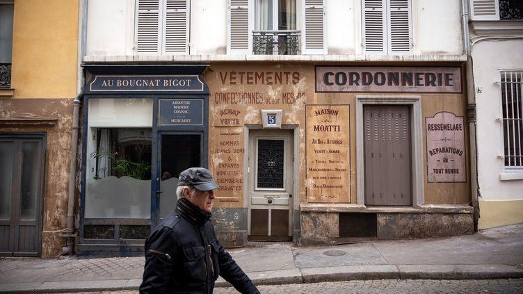 """Un homme passe dans undécor de cinéma abandonné à cause d'un tournage interrompu à Montmartre. Il s'agit dufilm """"Adieu Monsieur Haffman"""" que Fred Cavayé tournait avec Daniel Auteuil. (LIONEL BONAVENTURE / AFP)"""