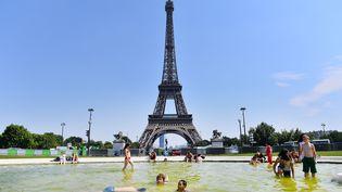 Des enfants se rafraîchissent dans une fontaine face à la Tour Eiffel à Paris, le 1er juillet 2015. (MUSTAFA YALCIN / ANADOLU AGENCY / AFP)