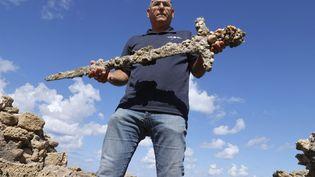 Un responsable de l'Autorité israélienne des Antiquités montre une épée vieille de 900 ans et ayant appartenu à un Croisé à Césarée (Israël), le 19 octobre 2021. (JACK GUEZ / AFP)