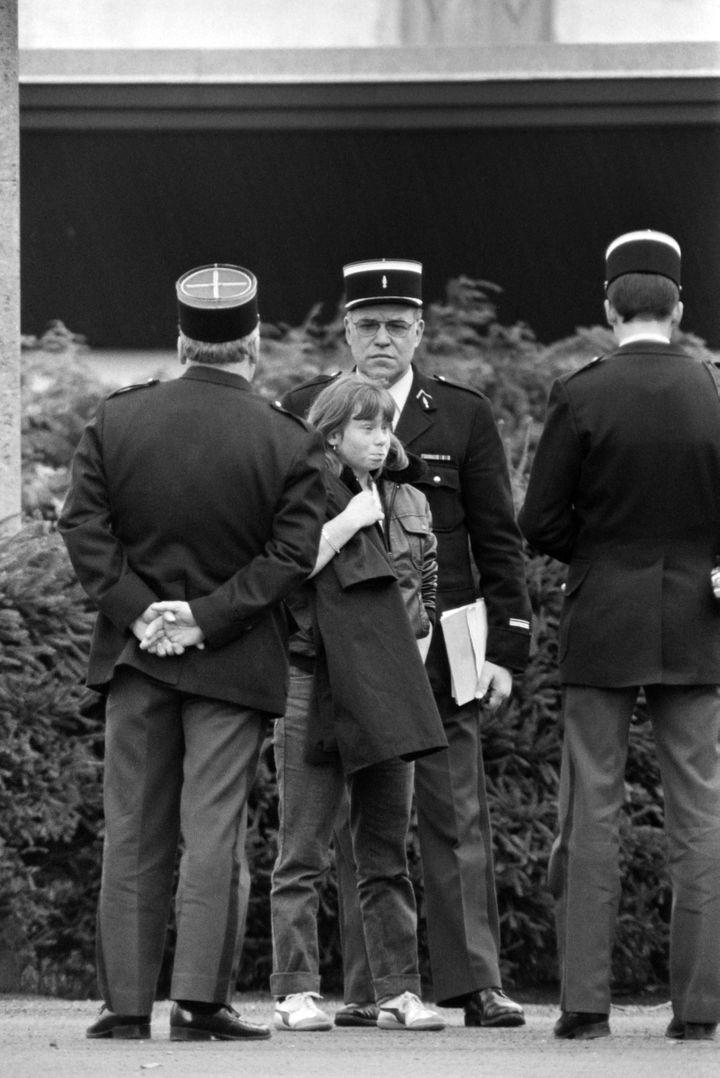 Murielle Bolle à l'âge de 15 ans et demi, entourée par les gendarmes, le 5 novembre 1984, à Epinal (Vosges). (JEAN-CLAUDE DELMAS / AFP)