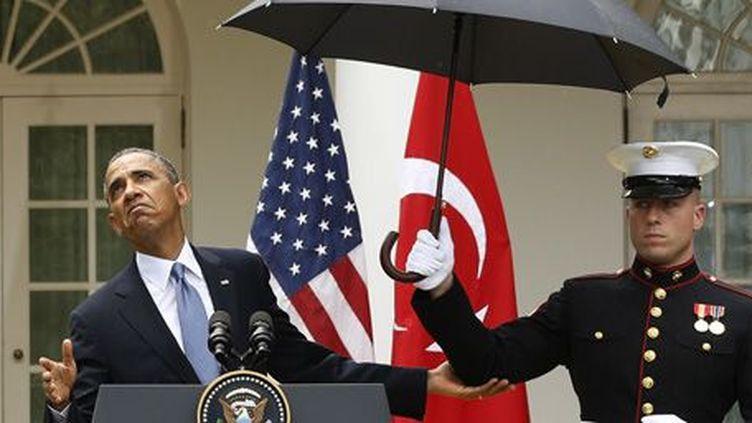 Le président des Etats-Unis, Barack Obama, vérifie s'il va pouvoir se passer d'un parapluie pendant une conférence de presse à la Maison blanche le 16-5-2013. (Reuters - Jason Reed)