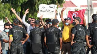 Des agents de sécurité interviennentlors d'affrontements entre des partisans du président tunisien Kaïs Saïedet des députés du parti Ennahdha,à Tunis le 26 juillet 2021. (MOHAMED HAMMI / SIPA / AFP)