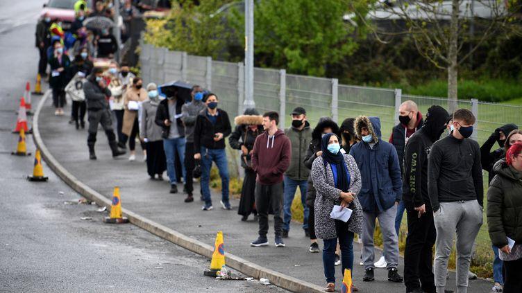 Des dizaines de personnes patientent devant un centre temporaire de vaccination ouvert à Bolton, dansle nord-ouest de l'Angleterre, le 17 mai 2021. (OLI SCARFF / AFP)