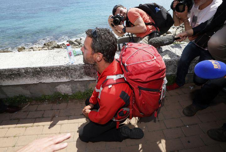Jérôme Kerviel s'agenouille alors qu'il arrive à proximité de la frontière franco-italienne, et de la ville de Menton, samedi 17 mai 2014. (JEAN-PAUL PELISSIER / REUTERS)