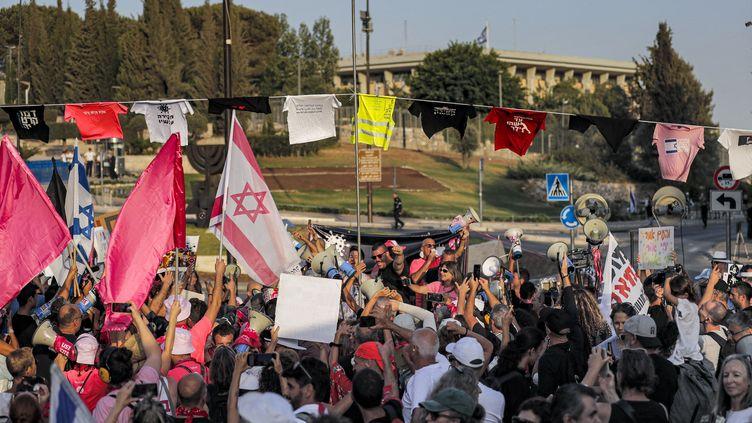 Des manifestants israéliens participant à un rassemblementdevant la Knesset pendant un vote du parlement le 13 juin 2021, en soutien à la nouvelle coalition qui devrait accéder au pouvoir en Israël. (AHMAD GHARABLI / AFP)