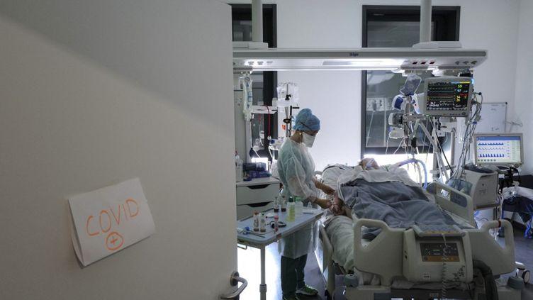 Un soignant prend en charge un patient atteint de Covid-19, le 22 avril 2021, à l'hôpital Pasteur de Colmar (Haut-Rhin). (SEBASTIEN BOZON / AFP)