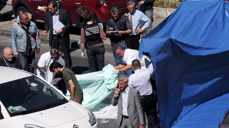 Des policiers sur les lieux d'un meurtre à Marseille (Bouches-du-Rhône), le 11 mai 2012. (ANNE-CHRISTINE POUJOULAT / AFP)